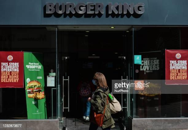 Woman wearing a face mask walks past Burger King restaurant on Grafton Street in Dublin. On Thursday, 13 May 2021, in Dublin, Ireland.