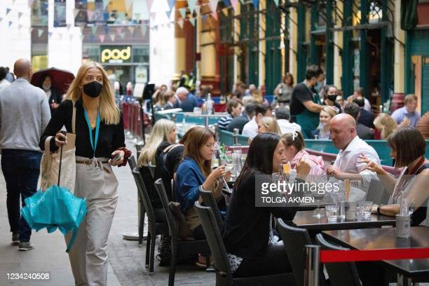 Woman wearing a face mask walks past shops and restaurants at Leadenhall Market in the City of London on July 27, 2021. - Prime Minister Boris...