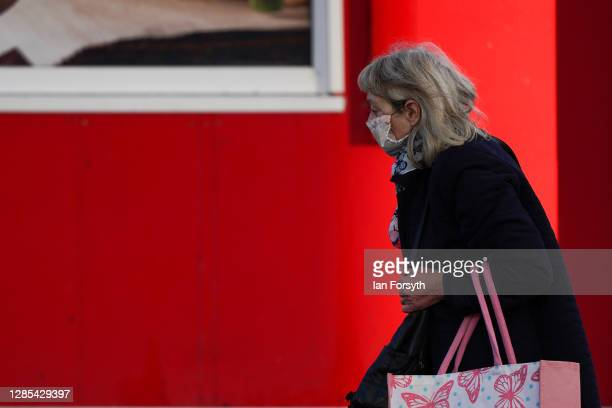 Woman wearing a face mask walks past shops in Hull on November 13, 2020 in Hull, England. Hull recorded 726.8 new cases per 100,000 people in the...