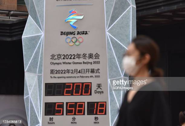 Woman wearing a face mask walks past the countdown clock showing 200 days to the 2022 Olympic Winter Games. 2022 Beijing Winter Olympic Games are...