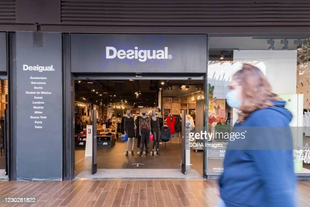 Woman wearing a face mask walks past the Desigual store at the Bonaire shopping center.