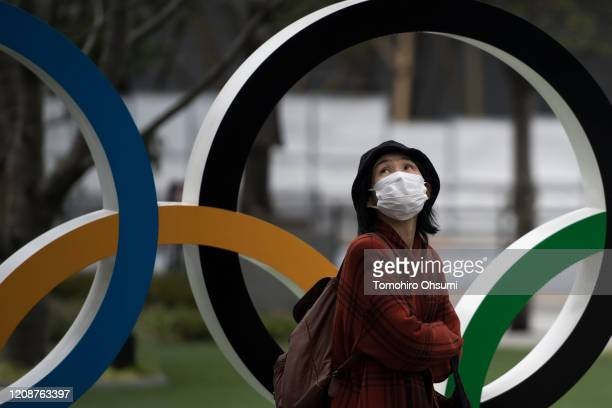 Woman wearing a face mask walks past the Olympic rings in front of the new National Stadium, the main stadium for the upcoming Tokyo 2020 Olympic and...