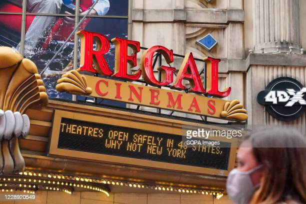 Woman wearing a face mask walks past the Regal Cinemas. Regal Cinemas which is the second-largest operator of theatres in the United States, plans to...