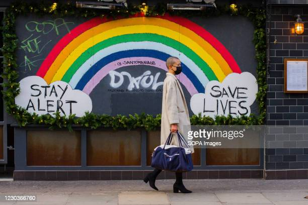 Woman wearing a face mask walks past the Stay Alert Save Lives Rainbow Sign in Soho. As daily Covid19 infection rate hits record high in London, the...