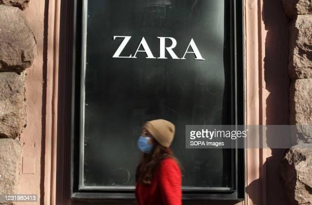 Woman wearing a face mask walks past ZARA logo of a Spanish apparel retailer at a window of a Zara brand store in Kiev.