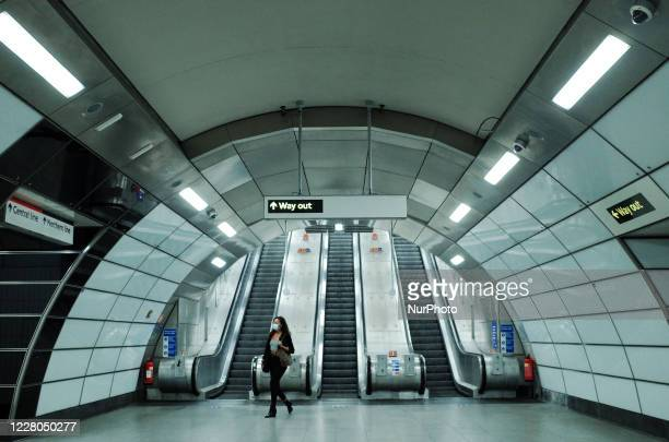 A woman wearing a face mask walks through a neardeserted Tottenham Court Road station in London England on August 14 2020 Passenger numbers on the...