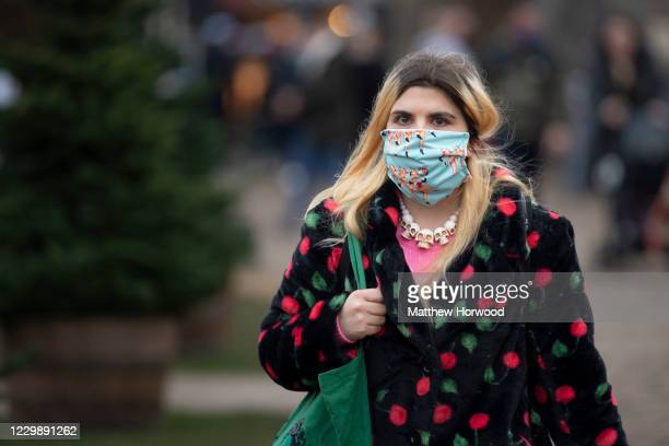 Woman wearing a face mask walks through Cardiff Castle on December 01, 2020 in Cardiff, Wales. From Friday at 6pm licensed pubs, cafes and...