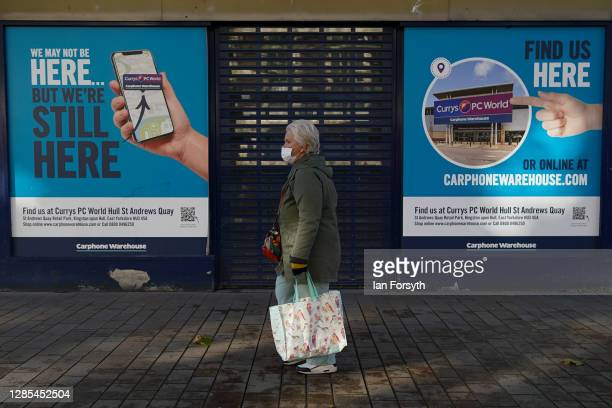 Woman wearing a face mask walks through Hull city centre on November 13, 2020 in Hull, England. Hull recorded 726.8 new cases per 100,000 people in...
