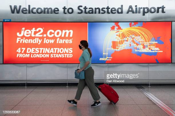 Woman wearing a face mask walks through the departures terminal at Stansted Airport on June 30, 2020 in Stansted, United Kingdom. Passengers...