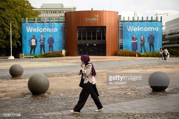Woman wearing a face mask walks through University Square past Coventry University's Alan Berry Building at the beginning of the new academic year,...