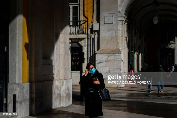Woman wearing a face mask walks under Rua Augusta arch in Lisbon on January 7, 2021. - Portugal reported a record 10,000 new coronavirus cases in 24...