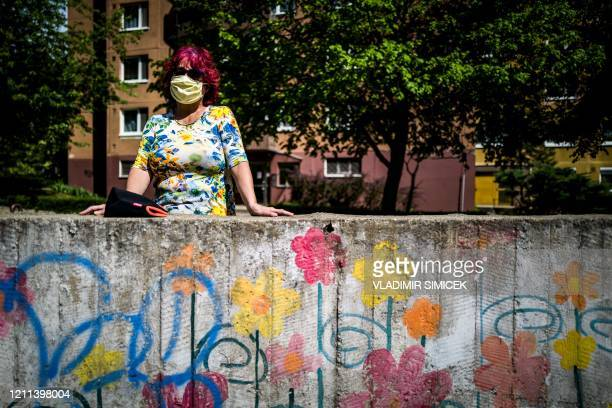Woman wearing a face mask watches a concert of a pianist in the middle of blocks of flats at Bratislava's suburb Devinska Nova Ves during the...