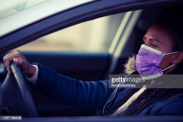 woman wearing a face mask while driving a car. - driving mask stock pictures, royalty-free photos & images