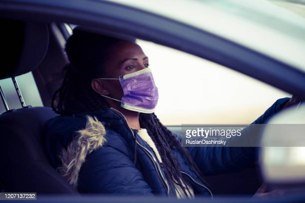woman wearing a face mask while driving a privet car. - driving mask stock pictures, royalty-free photos & images