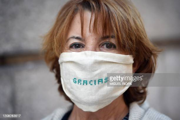 "Woman wearing a face mask with the word ""thanks"" embroidered poses in a street in Coruna, northwestern Spain, on March 26, 2020. - Spain's..."