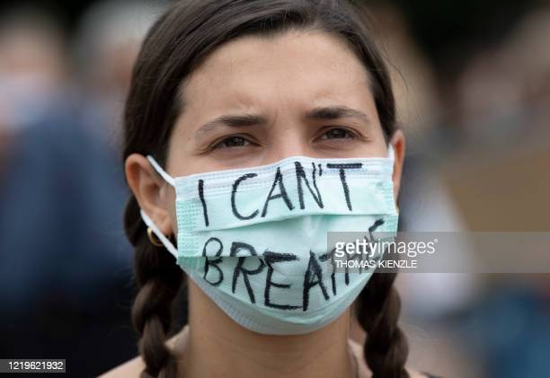 "Woman wearing a face mask with the words ""I can't breathe"" protests against racism and pays tribute to George Floyd during a Black Lives Matter..."