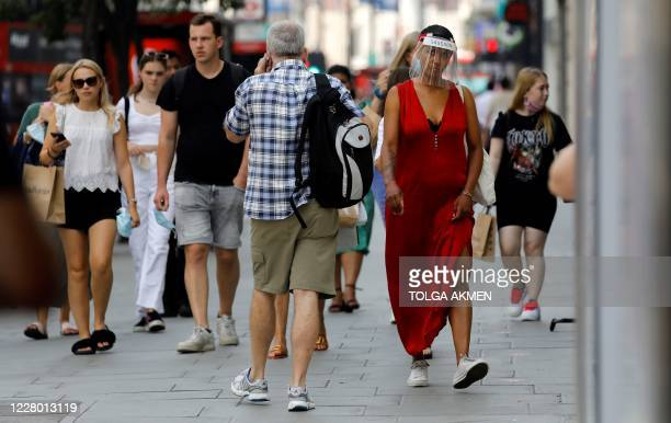 Woman wearing a face visor due to the COVID-19 pandemic, walks with shoppers past a shop in London on August 12, 2020. - Britain's economy contracted...