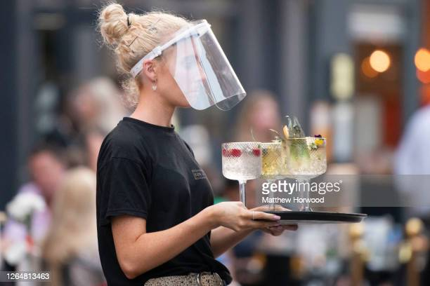 Woman wearing a face visor serves cocktails at Gin and Juice bar gin bar on August 08, 2020 in Cardiff, Wales. Coronavirus lockdown measures continue...