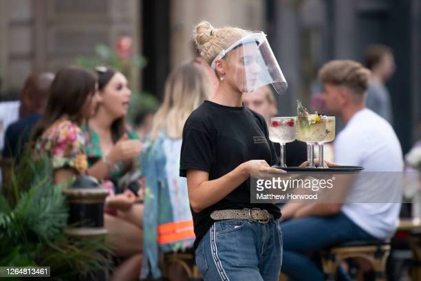 Woman wearing a face visor serves cocktails at Gin and Juice gin bar on August 08, 2020 in Cardiff, Wales. Coronavirus lockdown measures continue to...