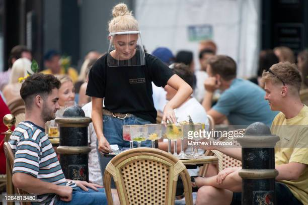 Woman wearing a face visor serves drinks at Gin and Juice gin bar on August 08, 2020 in Cardiff, Wales. Coronavirus lockdown measures continue to be...