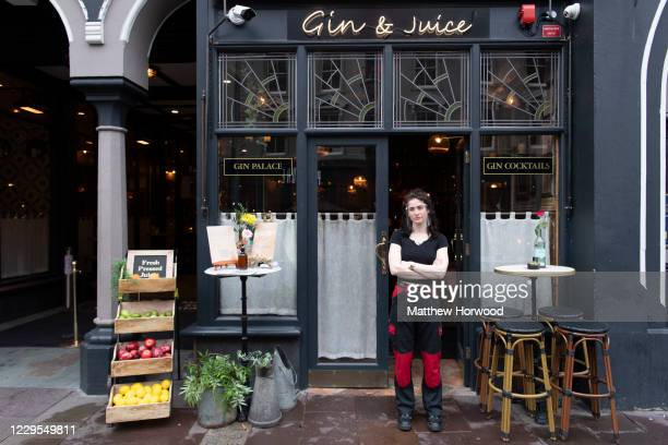 Woman wearing a face visor waits for customers outside Gin and Juice bar on November 9, 2020 in Cardiff, Wales. Wales' health minister said cases are...