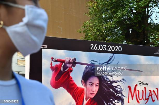 A woman wearing a facemask amid concerns about the spread of the COVID19 novel coronavirus waits to cross the street in front of a poster for the...