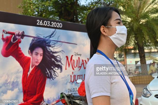 Woman, wearing a facemask amid concerns about the spread of the COVID-19 novel coronavirus, waits to cross the street in front of a poster for the...