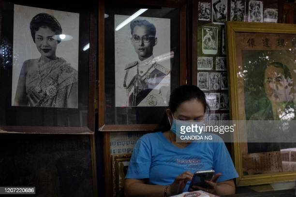 Woman, wearing a facemask amid concerns over the spread of the COVID-19 novel coronavirus, sits in front of portraits of Thailand's former queen...