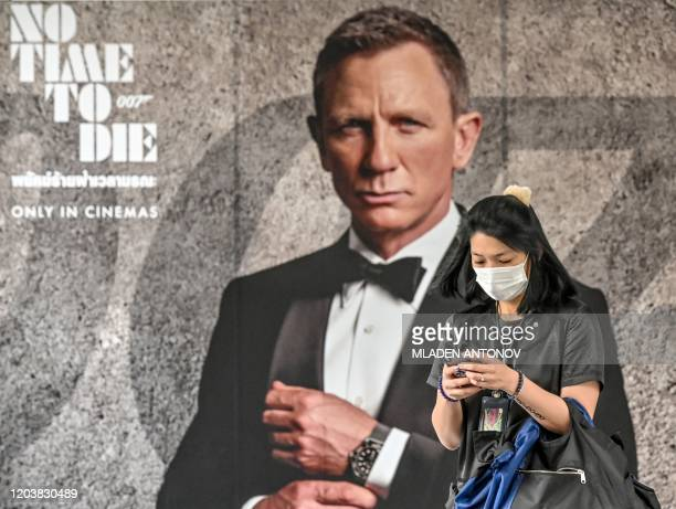 "Woman wearing a facemask amid fears of the spread of the COVID-19 novel coronavirus walks past a poster for the new James Bond movie ""No Time to Die""..."
