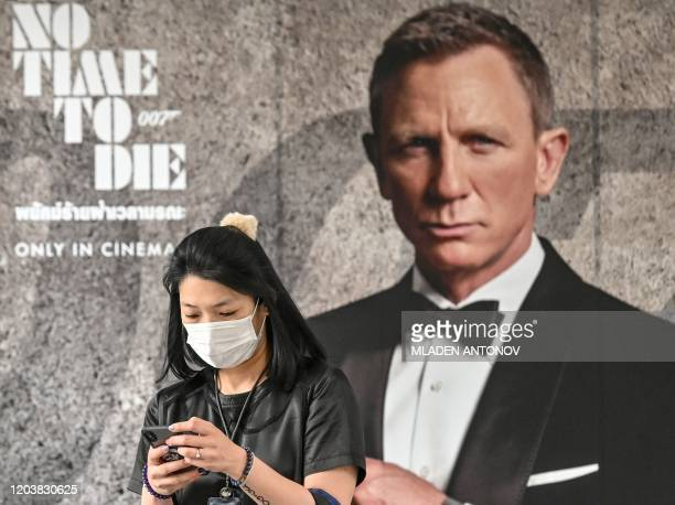 A woman wearing a facemask amid fears of the spread of the COVID19 novel coronavirus walks past a poster for the new James Bond movie No Time to Die...