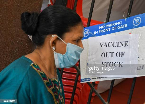 Woman wearing a facemask as a precaution against the spread of covid-19 seen reading a poster saying 'vaccine out of stock' outside a vaccination...