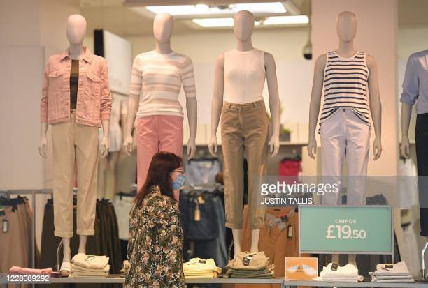 Woman wearing a facemask as a precaution against the spread of the novel coronavirus is seen inside a branch of the clothing and food retailer Marks...