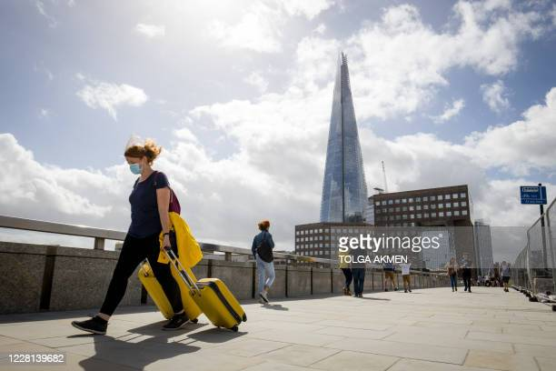 Woman wearing a facemask as a precaution against the spread of the novel coronavirus drags her suitcases on London Bridge with the Shard tower in the...
