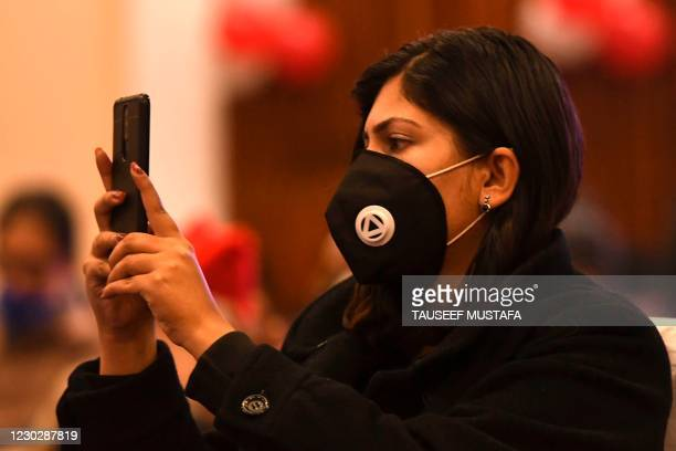 Woman wearing a facemask as a preventive measure against the Covid-19 coronavirus takes pictures with her mobile phone during a function organised by...