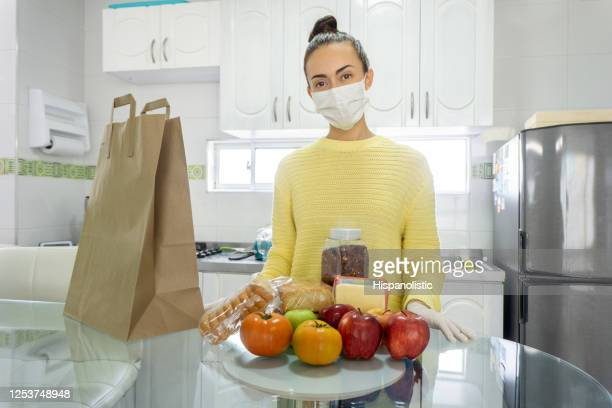 woman wearing a facemask  at home organizing the groceries after shopping - biosecurity stock pictures, royalty-free photos & images