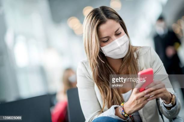 woman wearing a facemask at the airport while texting - biosecurity stock pictures, royalty-free photos & images