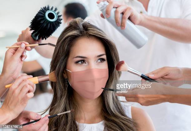woman wearing a facemask at the beauty salon while getting her makeup done - glamour stock pictures, royalty-free photos & images
