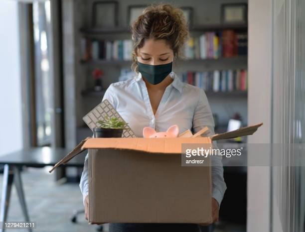 woman wearing a facemask at the office while holding a box with her belongings after being fired from her job - quitting a job stock pictures, royalty-free photos & images