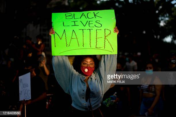 A woman wearing a facemask holds a placard during a Justice for George Floyd event in Houston Texas on May 30 after George Floyd an unarmed black...