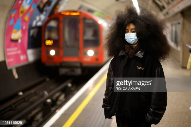 Woman wearing a facemask poses while she waits on a platform for a train on the Underground in central London on February 12, 2021.