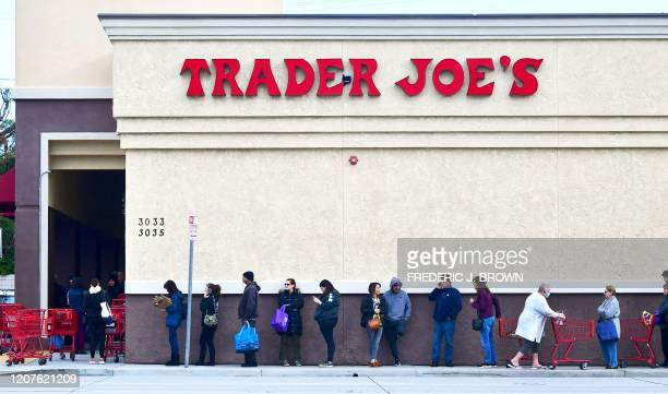 Woman wearing a facemask pushes her cart to the back of the line as people line up before the opening of a Trader Joe's store in Pasadena, Caifornia...