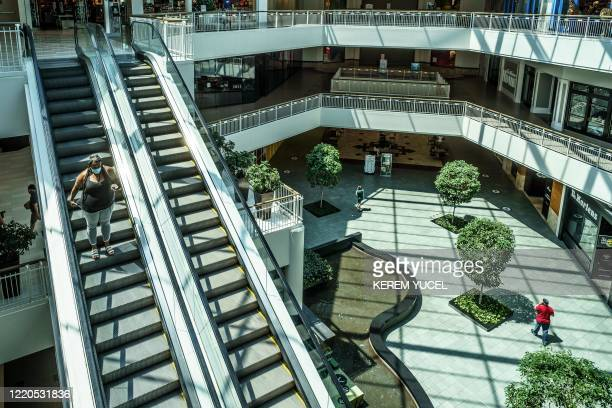 Woman wearing a facemask rides down the escalator at the Mall of America on June 16, 2020 in Bloomington, Minnesota, after some of the shops at the...