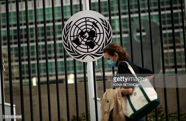 Woman wearing a facemask runs past the United Nations headquarters in New York on March 11 one year after the pandemic was officially declared. - The...