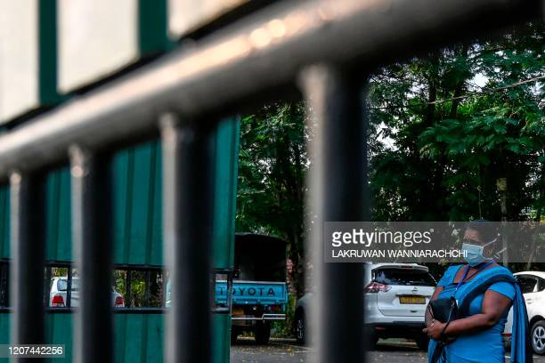 A woman wearing a facemask stands at the entrance of Sri Lanka's Infectious Diseases Hospital near Colombo on March 17 2020