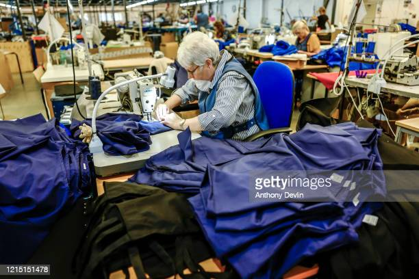 Woman wearing a facemask stitches NHS uniforms as staff at Tibard begin work on a new order of 20,000 nurses uniforms at their factory in Dukinfield...