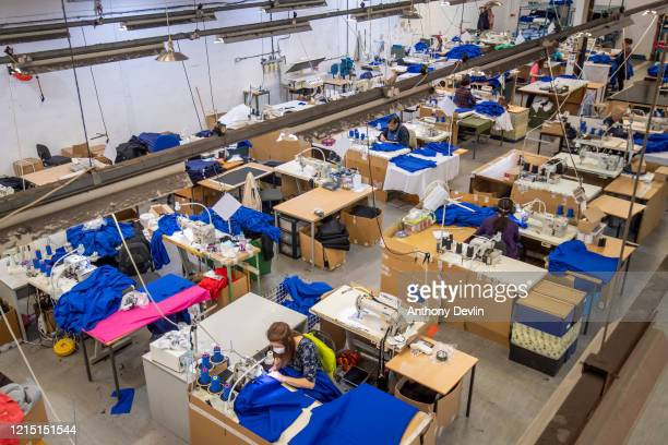 A woman wearing a facemask stitches NHS uniforms as staff at Tibard begin work on a new order of 20000 nurses uniforms at their factory in Dukinfield...