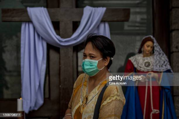 A woman wearing a facemask walks past a cross and a statue of Mary outside a closed church amid government orders for everyone to stay home to avoid...