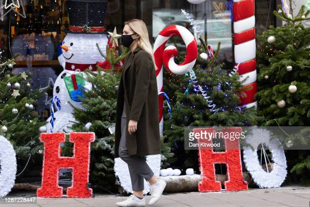 Woman wearing a facemask walks past Christmas decorations outside a wine shop in Mayfair on November 23, 2020 in London, England. UK Prime Minister,...