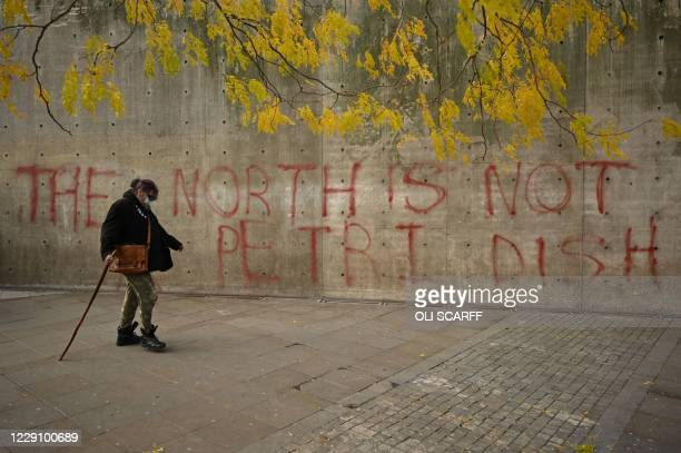 Woman wearing a face-mask walks past graffiti declaring that 'the north is not a petri dish' after Greater Manchester mayor Andy Burnham threatened...