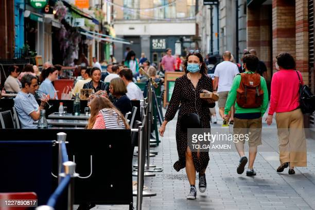 """Woman wearing a facemask walks past outdoor diners in London on August 3 as the Government's """"Eat out to Help out"""" coronavirus scheme to get..."""